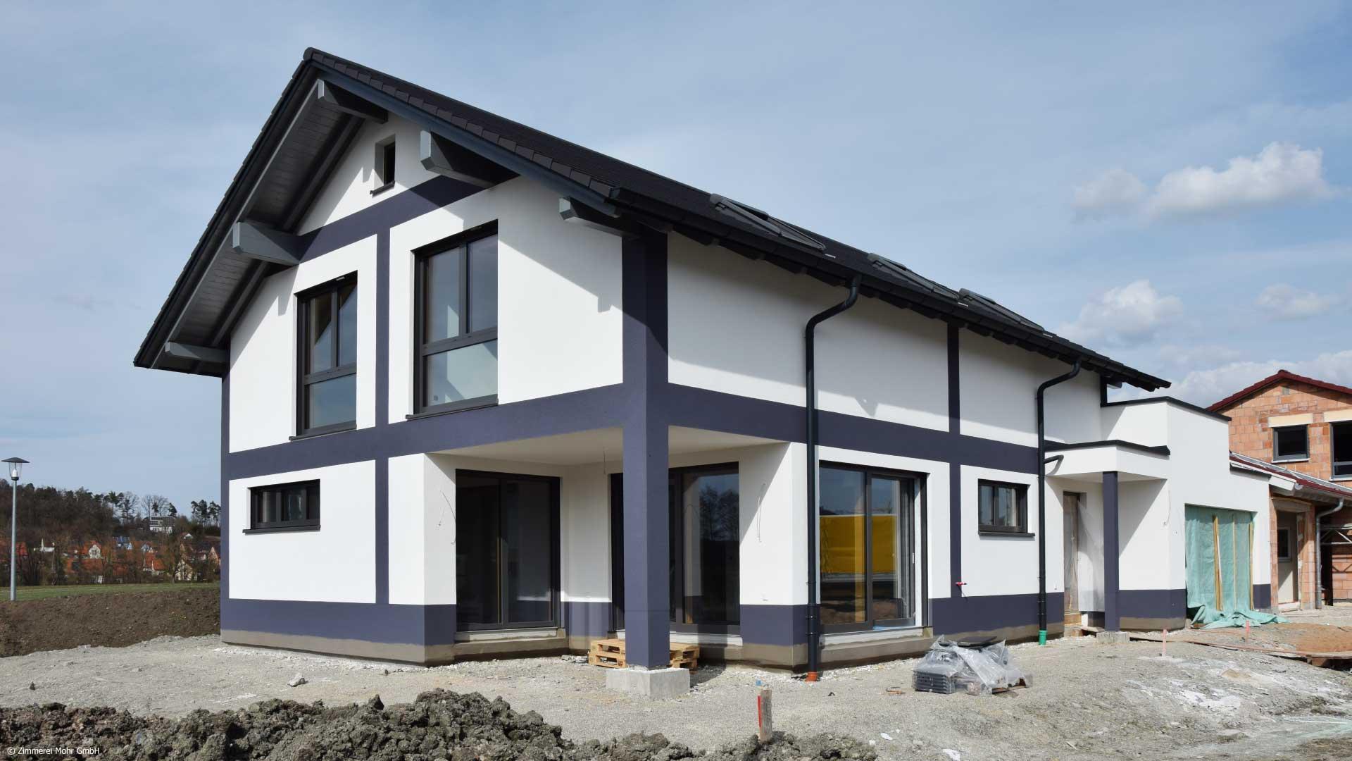 Familienhaus DESIGN – Neubau Holzhaus mit Putzfassade im Fachwerk Look